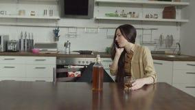 Μεθυσμένη γυναίκα που κουβεντιάζει στο τηλέφωνο στην εσωτερική κουζίνα απόθεμα βίντεο