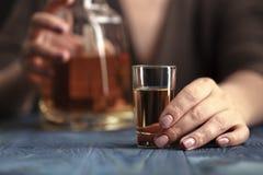 Μεθυσμένη γυναίκα που κρατά ένα οινοπνευματώδες ποτό, που στρέφεται στο ποτό Στοκ Εικόνα