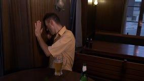 Μεθυσμένη συνεδρίαση τύπων σε έναν πίνακα σε ένα μπαρ και μια μπύρα κατανάλωσης - απόθεμα βίντεο