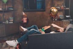 Μεθυσμένος γενειοφόρος νεαρός άνδρας με τις ιδιαίτερες προσοχές που βρίσκονται στον καναπέ Στοκ φωτογραφίες με δικαίωμα ελεύθερης χρήσης
