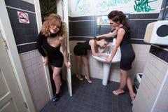 Μεθυσμένο κορίτσι στους φραγμούς τουαλετών γυναίκες το βράδυ στοκ εικόνα