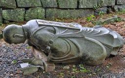 Μειωμένος κάτω, πεσμένη βουδιστική πέτρα γρανίτη μοναχών αγαλματώδης σε έναν ναό στην Ιαπωνία Ναός Honmyo Higo, νομαρχιακό διαμέρ στοκ φωτογραφίες