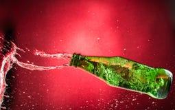 Μειωμένο πετάγματος και συντρίβοντας πράσινο μπουκάλι σε ένα κόκκινο υπόβαθρο, τα shards και τους παφλασμούς κλίσης στοκ εικόνες