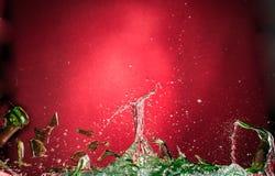 Μειωμένο πετάγματος και συντρίβοντας πράσινο μπουκάλι σε ένα κόκκινο υπόβαθρο, τα shards και τους παφλασμούς κλίσης στοκ φωτογραφία με δικαίωμα ελεύθερης χρήσης
