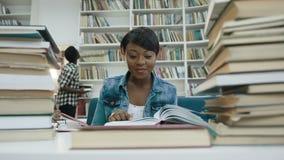 Μελέτη γυναικών σπουδαστών χαμόγελου αφρικανική, που διαβάζει το βιβλίο στη σύγχρονη βιβλιοθήκη απόθεμα βίντεο