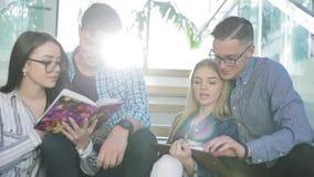 Μελέτη σπουδαστών, που διαβάζει το εκπαιδευτικό βιβλίο στο κολλέγιο απόθεμα βίντεο