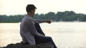 Μελαγχολική αρσενική συνεδρίαση εφήβων μόνο στην πέτρα κοντά στον ποταμό και τη σκέψη για τη ζωή απόθεμα βίντεο