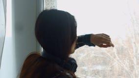 Μελαγχολική νέα γυναίκα που κλίνει στο παράθυρο απόθεμα βίντεο