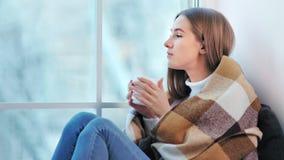 Μελαγχολική νέα ελκυστική γυναίκα που απολαμβάνει το Σαββατοκύριακο που κάθεται στο σπίτι στον καφέ κατανάλωσης παραθύρων φιλμ μικρού μήκους
