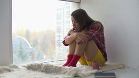 Μελαγχολική συνεδρίαση γυναικών στο πάτωμα που φαίνεται έξω παράθυρο απόθεμα βίντεο
