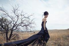 Μελαχροινή βασίλισσα στο πάρκο Μαύρο φόρεμα φαντασίας στοκ φωτογραφία