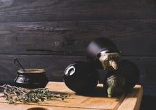 Μελιτζάνα στα κλωστοϋφαντουργικά προϊόντα με την ξηρά χλόη σε ένα στρογγυλό κύπελλο στην ξύλινη χλεύη επάνω, εκλεκτής ποιότητας μ Στοκ Φωτογραφίες