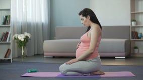 Μελλοντική μητέρα που κάνει τις τεντώνοντας ασκήσεις που παίρνουν έτοιμες για τον τοκετό στο σπίτι απόθεμα βίντεο