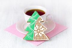 Μελόψωμο χριστουγεννιάτικων δέντρων με το φλυτζάνι coffe στον ξύλινο πίνακα με τη ρόδινη πετσέτα Στοκ Φωτογραφίες