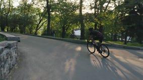 Μεμβρανοειδής αθλητικός ποδηλάτης που ανέρχεται το λόφο στο πάρκο Ποδηλάτης προς τα κάτω στο πάρκο Οδικός ποδηλάτης απόθεμα βίντεο