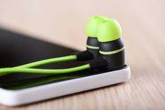 Μεμονωμένα ακουστικά στην οθόνη smartphone Αντανάκλαση των ακουστικών στην οθόνη smartphone στοκ εικόνα με δικαίωμα ελεύθερης χρήσης