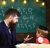 Μεμονωμένη έννοια μαθήματος Ο δάσκαλος με τη γενειάδα, πατέρας διδάσκει λίγο γιο στην τάξη, πίνακας κιμωλίας στο υπόβαθρο αγόρι Στοκ Φωτογραφία