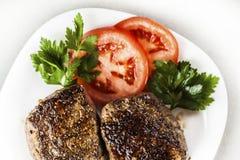 Μενταγιόν σε ένα πιάτο με τις φέτες της ντομάτας Στοκ Φωτογραφία
