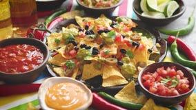 Μεξικάνικα πικάντικα τσιπ nacho καλαμποκιού που εξυπηρετούνται με το λειωμένο τυρί απόθεμα βίντεο