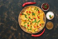 Μεξικάνικα τσιπ nachos με τις σάλτσες στο σκοτεινό αγροτικό υπόβαθρο Τοπ άποψη, διάστημα αντιγράφων στοκ φωτογραφία