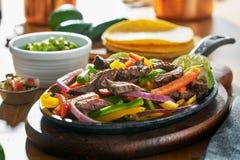Μεξικάνικα fajitas βόειου κρέατος στο skillet σιδήρου με τα πιπέρια κουδουνιών και guacamole στην πλευρά στοκ φωτογραφίες με δικαίωμα ελεύθερης χρήσης