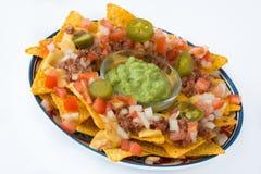 Μεξικάνικα nachos με το βόειο κρέας, guacamole, τη σάλτσα τυριών, τα πιπέρια, την ντομάτα και το κρεμμύδι στο πιάτο που απομονώνε Στοκ Φωτογραφία
