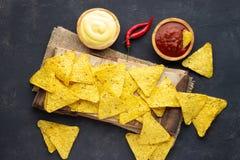 Μεξικάνικα nachos τσιπ καλαμποκιού με τις σάλτσες στο σκοτεινό υπόβαθρο στοκ φωτογραφία με δικαίωμα ελεύθερης χρήσης
