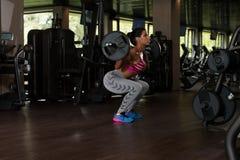 Μεξικάνικη γυναίκα που κάνει τη στάση οκλαδόν Barbell άσκησης Στοκ Εικόνα