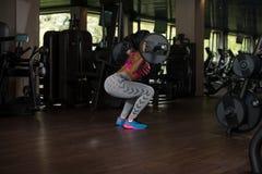 Μεξικάνικη γυναίκα που κάνει τη στάση οκλαδόν Barbell άσκησης Στοκ Εικόνες