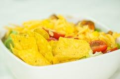 Μεξικάνικη σαλάτα κινηματογραφήσεων σε πρώτο πλάνο στο άσπρο κύπελλο, τα κίτρινες tortilla τσιπ και τις ντομάτες ορατά Στοκ Φωτογραφία