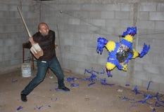 Μεξικάνικο άτομο που χτυπά το pinata με το φτυάρι Στοκ εικόνα με δικαίωμα ελεύθερης χρήσης