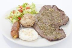 Μερίδα του κρέατος με τη σαλάτα arepa λουκάνικων και καλαμποκιού Στοκ Φωτογραφίες
