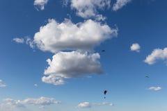 Μερικά ανεμόπτερα που πετούν ενάντια όμορφο σε έναν βαθύ, μπλε ουρανός, με τα μεγάλα άσπρα σύννεφα Στοκ εικόνες με δικαίωμα ελεύθερης χρήσης