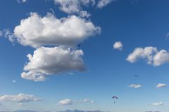 Μερικά ανεμόπτερα που πετούν ενάντια όμορφο σε έναν βαθύ, μπλε ουρανός, με τα μεγάλα άσπρα σύννεφα Στοκ Φωτογραφία