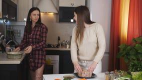 Μερικά κορίτσια στην κουζίνα που προετοιμάζει το κοτόπουλο έψησαν στο φούρνο και κατοχή της διασκέδασης μιλώντας φιλμ μικρού μήκους