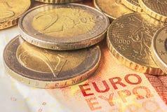 Μερικά νομίσματα του ευρώ σε ένα τραπεζογραμμάτιο δέκα ευρώ Στοκ εικόνα με δικαίωμα ελεύθερης χρήσης