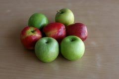 Μερικά πράσινα και κόκκινα μήλα σε έναν ξύλινο πίνακα Στοκ φωτογραφίες με δικαίωμα ελεύθερης χρήσης