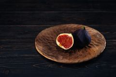 Μερικά σύκα σε ένα πιάτο σε ένα μαύρο ξύλινο υπόβαθρο στοκ φωτογραφία