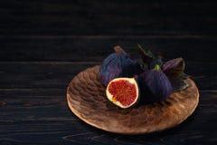 Μερικά σύκα σε ένα πιάτο σε ένα μαύρο ξύλινο υπόβαθρο στοκ εικόνες με δικαίωμα ελεύθερης χρήσης
