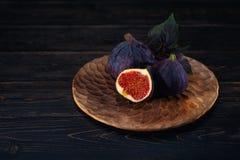 Μερικά σύκα σε ένα πιάτο σε ένα μαύρο ξύλινο υπόβαθρο στοκ φωτογραφίες