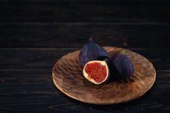 Μερικά σύκα σε ένα πιάτο σε ένα μαύρο ξύλινο υπόβαθρο στοκ εικόνες