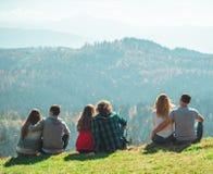 Μερικά ταξιδιωτικά αγόρια και κορίτσια ζεύγους που κάθονται νέο οικογενειακό ταξίδι έννοιας τρόπου ζωής συγκινήσεων απότομων βράχ στοκ φωτογραφία με δικαίωμα ελεύθερης χρήσης