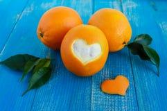 Μερικά ώριμα πορτοκάλια με τα φύλλα σε ένα μπλε ξύλινο υπόβαθρο Στοκ φωτογραφίες με δικαίωμα ελεύθερης χρήσης