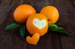 Μερικά ώριμα πορτοκάλια με τα φύλλα σε ένα σκοτεινό ξύλινο υπόβαθρο Στοκ Εικόνες