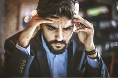 Μερικές φορές η μεγάλη επιχείρηση κάνει έναν μεγάλο πονοκέφαλο Νεαρός άνδρας Στοκ εικόνα με δικαίωμα ελεύθερης χρήσης