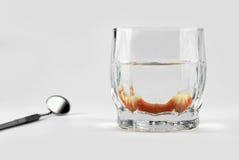 Μερική οδοντοστοιχία μέσα στο γυαλί δίπλα στον οδοντικό καθρέφτη Στοκ εικόνα με δικαίωμα ελεύθερης χρήσης