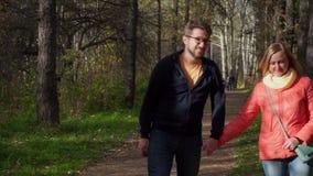 Μερικοί μέσης ηλικίας άνθρωποι περπατούν στο πάρκο Κρατούν τα χέρια απόθεμα βίντεο