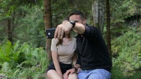 Μερικοί τουρίστες στηρίζονται στα ξύλα και selfie στις πέτρες κάτω από ένα δέντρο απόθεμα βίντεο