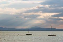 Μερικός κενός, λίγο sailboat σε μια λίμνη, κάτω από έναν ευμετάβλητο ουρανό με τις ακτίνες ήλιων που φιλτράρουν κατευθείαν στοκ φωτογραφία