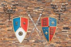 Μεσαιωνικά όπλα και κηροπήγια σε έναν τουβλότοιχο Στοκ Φωτογραφίες